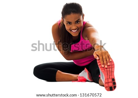 Beautiful young girl doing stretching exercise isolated on white. - stock photo