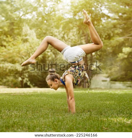 Beautiful young girl doing stretching exercise on green grass at park. Healthy lifestyle. Yoga - stock photo