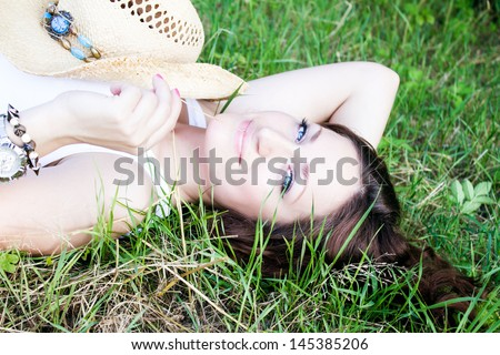 Beautiful young girl dreams, lying on the meadow in green grass