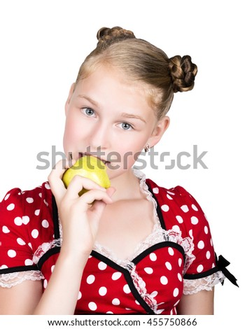 beautiful young girl dressed in a red dress with white polka dots eating an apple. healthy food - strong teeth concept. - stock photo