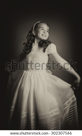 Beautiful young girl dressed in white, dancing like a princess. First Communion. Perfect teeth and smile, long curly hair. Dark background, studio shoot. Sepia picture. - stock photo