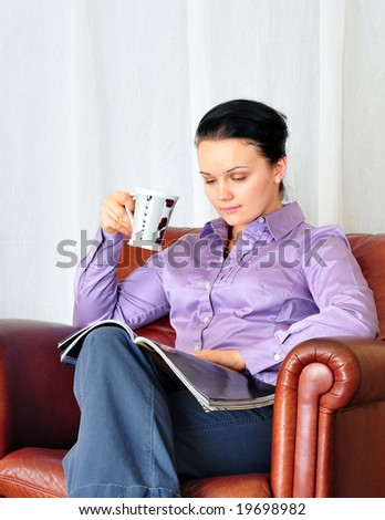 beautiful young girl drinking coffee and reading magazine - stock photo