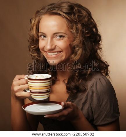 Beautiful young girl drinking tea or coffee - stock photo