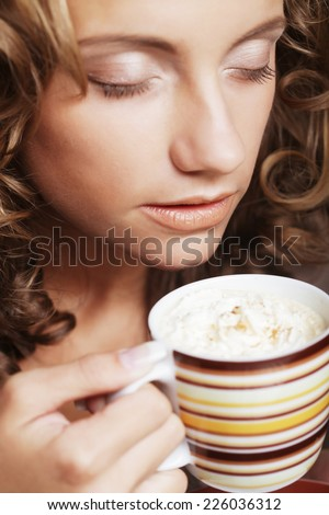 Beautiful young girl drinking tea or coffee - stock photo