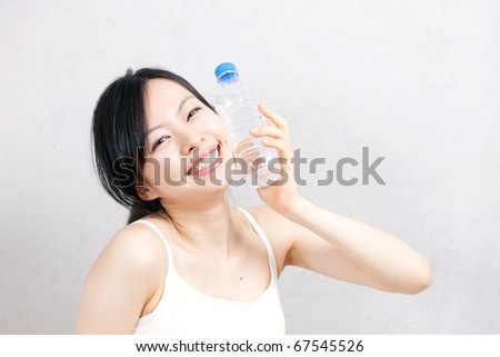 beautiful young girl drinking water after exercise