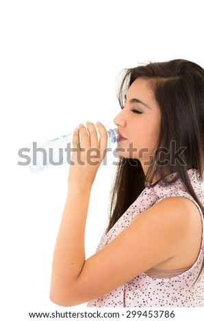 Beautiful young girl drinking water from a plastic bottle side view isolated on white - stock photo