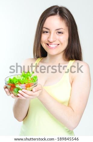 beautiful young girl eating salad. smiling happy girl eating healthy food. - stock photo