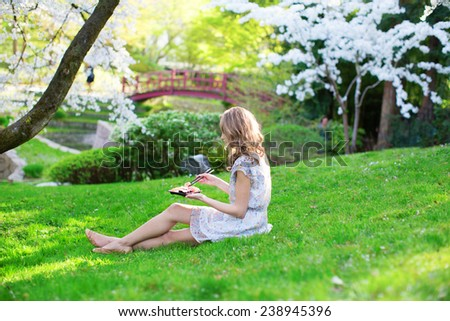 Beautiful young girl eating sushi in cherry blossom garden on a spring day - stock photo