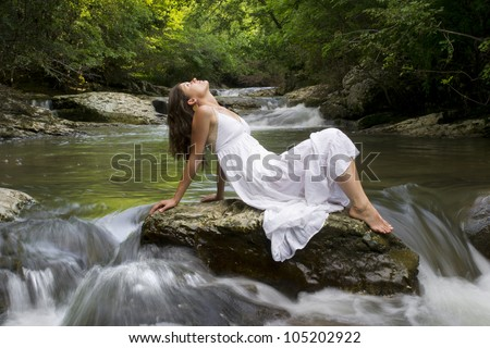 Beautiful young girl enjoying the purifying herself in the clear water of a mountain stream