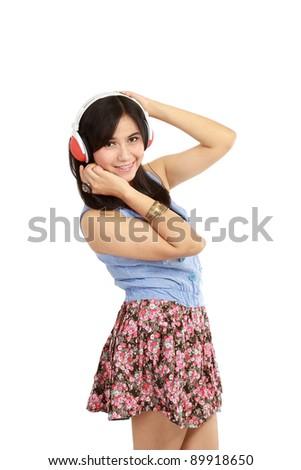 beautiful young girl enjoys listening music. Isolated white background - stock photo