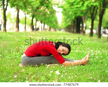 Beautiful young girl exercising in a park - stock photo