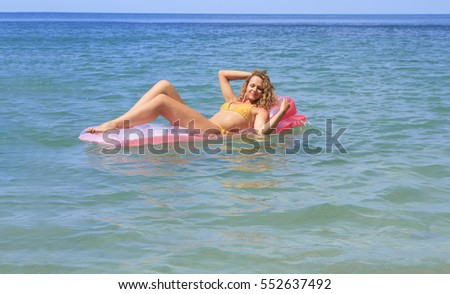 Beautiful young girl floating on a mattress in the sea