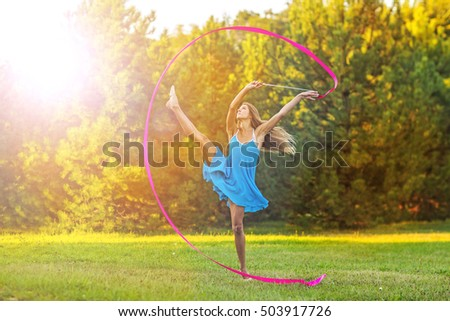 beautiful young girl flying in a jump with gymnastic ribbon. Autumn park on a sunny day. Girl dressed in blue dress, pink ribbon gymnastics