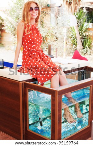 Beautiful young girl gets fish spa procedure in a beautiful blue water
