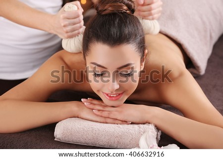 Beautiful young girl having massage with herbal balls in spa salon - stock photo