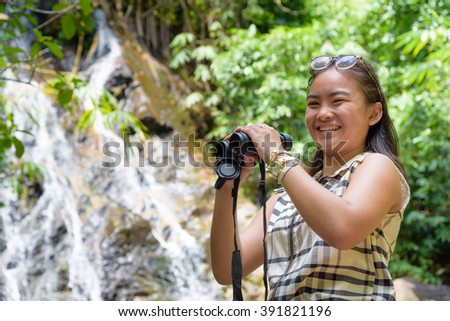 Beautiful young girl hiking is using binoculars look for birds smiling to the camera in tropical forest near the waterfalls in Thailand - stock photo