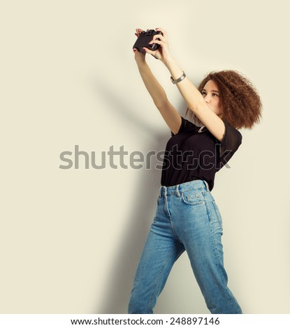 beautiful young girl hipster takes photos, shoots selfe, taking pictures of himself on camera in jeans and a black t-shirt in the Studio - stock photo