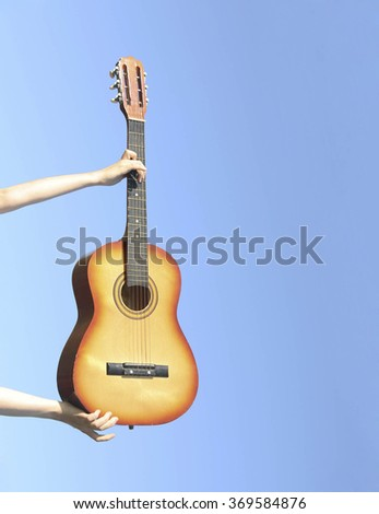 Beautiful young girl hold her guitar against blue summer sky.