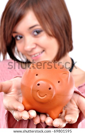Beautiful young girl holding a piggy bank - stock photo