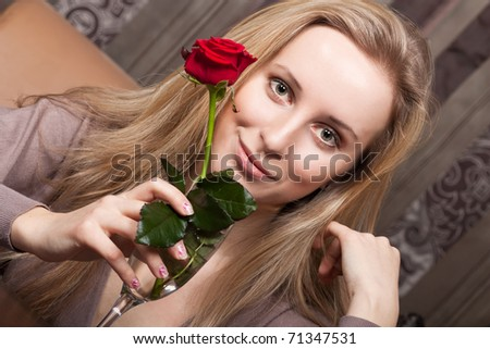 Beautiful young girl holding a red rose - stock photo