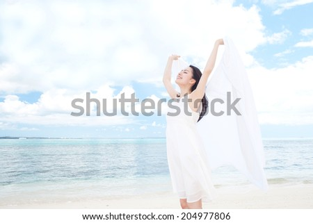 Beautiful young girl holding white cloth on tropical island beach - stock photo