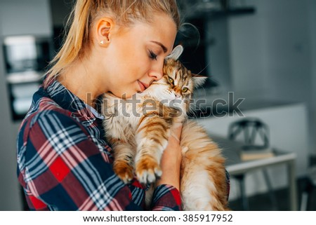 Beautiful young girl holging her ginger cat. Bestfriends - stock photo