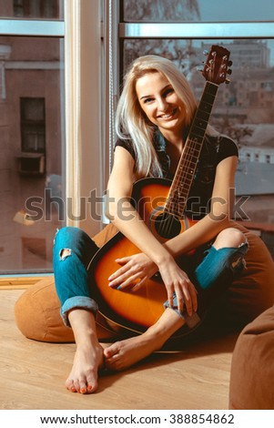 beautiful young girl hugging a guitar with hands and smiles at the camera. Girl with guitar. Woman playing guitar. leisure with guitar. - stock photo