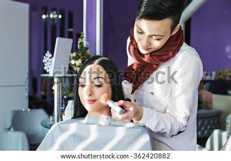 Beautiful young girl in a beauty salon. Job hairdresser and stylist. Doing make-up. A brush for applying powder. A girl with long black hair in a chair at the make-up artist. Purple background.  - stock photo