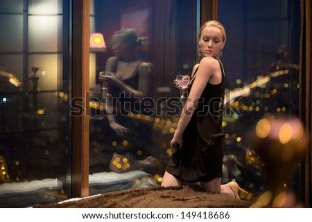 Beautiful young girl in a black dress with glass sitting on the bed  - stock photo