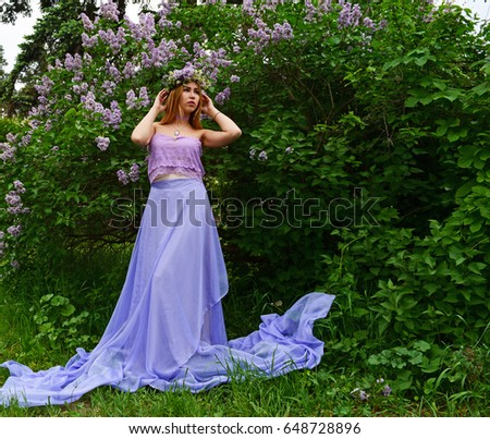 Beautiful young girl in a blue gown near lilac