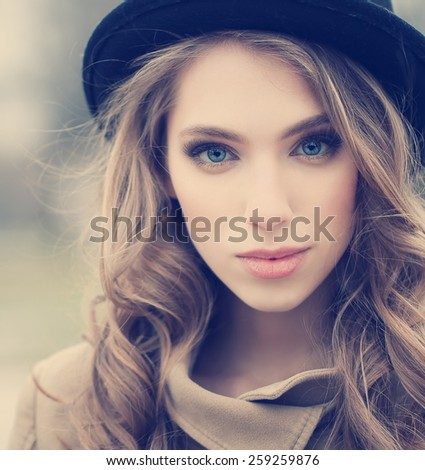 Beautiful young girl in a hat outdoors - stock photo