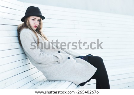 beautiful young girl in a hat sitting on a bench - stock photo