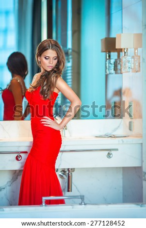 Beautiful young girl in a red dress - stock photo