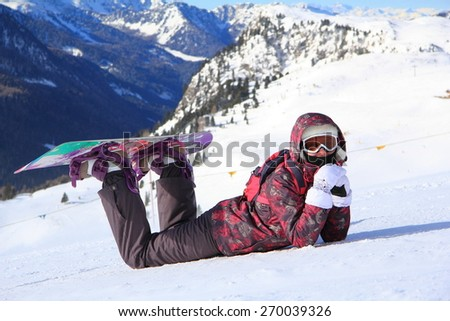 beautiful young girl in a ski suit with a snowboard posing in the snow mountains in the background - stock photo
