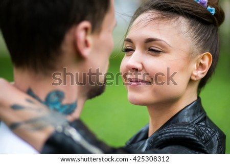 Beautiful young girl in a white dress and black leather jacket with tattoos hugging her boyfriend - stock photo