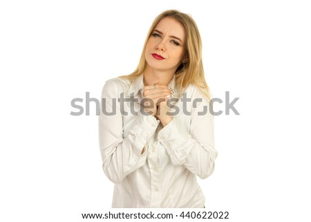 beautiful young girl in a white shirt looks into the camera and squeezes hands