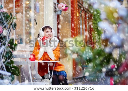 Beautiful young girl in an outdoor Parisian cafe on a winter day, drinking hot beverage during snowfall
