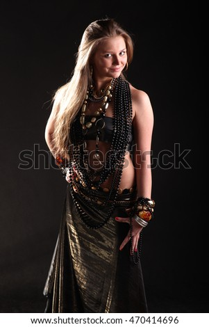 beautiful young girl in beads and bracelets on black background