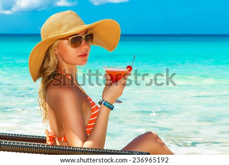 Beautiful young girl in bikini is sitting on a sun lounger coast of tropical sea and enjoying cocktail. Summer vacation concept. - stock photo