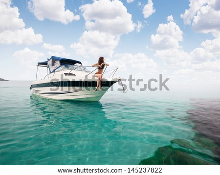 Beautiful young girl in bikini posing on a yacht at a sunny summer day  - stock photo
