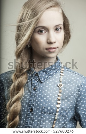 beautiful young girl in blue shirt with bead