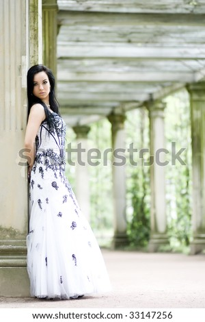Beautiful young girl in elegant dress in summerhouse - stock photo