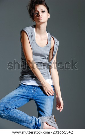 beautiful young girl in jeans posing on gray background  - stock photo
