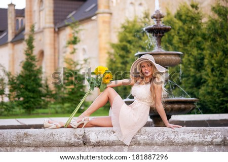 Beautiful young girl in light dress, sitting in the fabulous garden, holding bouquet of sunflowers  - stock photo