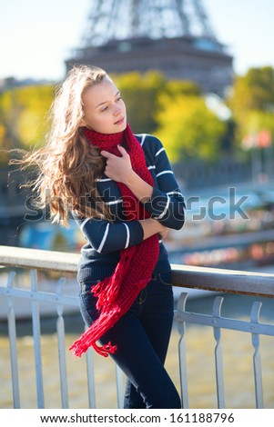 Beautiful young girl in red scarf on a fall day in Paris - stock photo