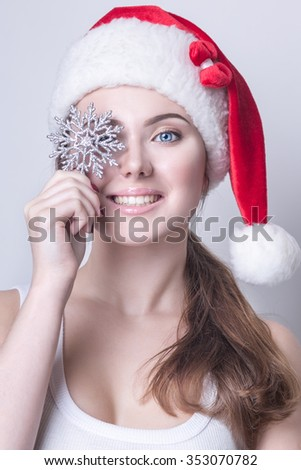 Beautiful young girl in Santa hat closes one eye, a silver snowflake, Christmas, New Year - stock photo