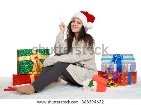 beautiful young girl in santa hat with big snowflake toy and gift boxes, white background - stock photo