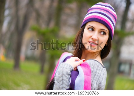 Beautiful young girl in striped hat at park - stock photo