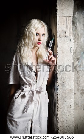 Beautiful young girl in the image of nurse with syringe in hand standing by the wall - stock photo