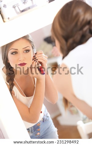 Beautiful young girl in the mirror preparing  - stock photo